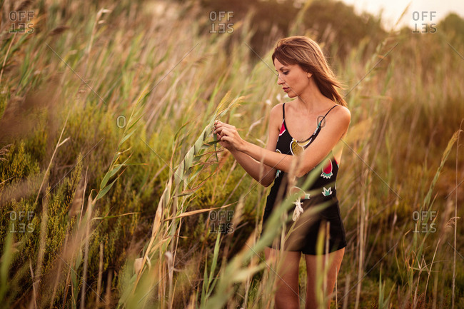 Woman in summer outfit standing in field grass