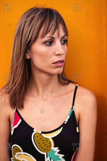 Stylish woman on sandy beach against orange container