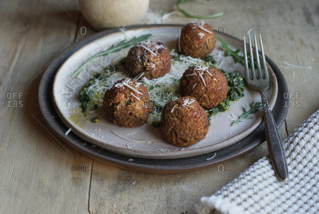 Close-up of plate with served lentil meatballs garnished with rucola pesto sauce and cheese on table