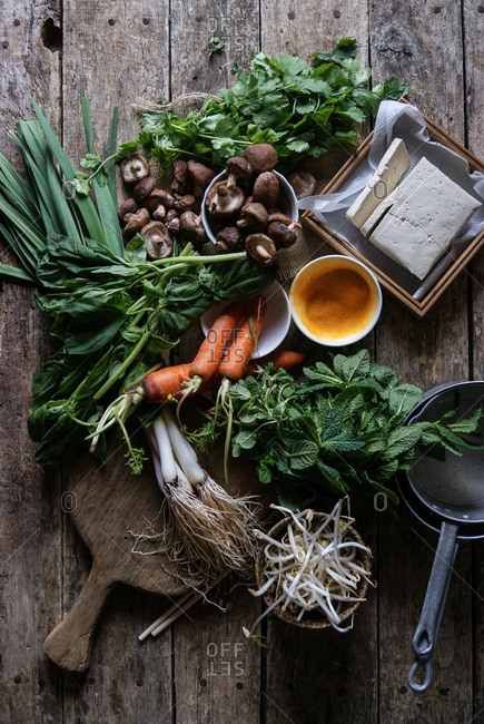 Flat lay of arranged vegetables on rustic table for preparing traditional crepe Banh Xeo
