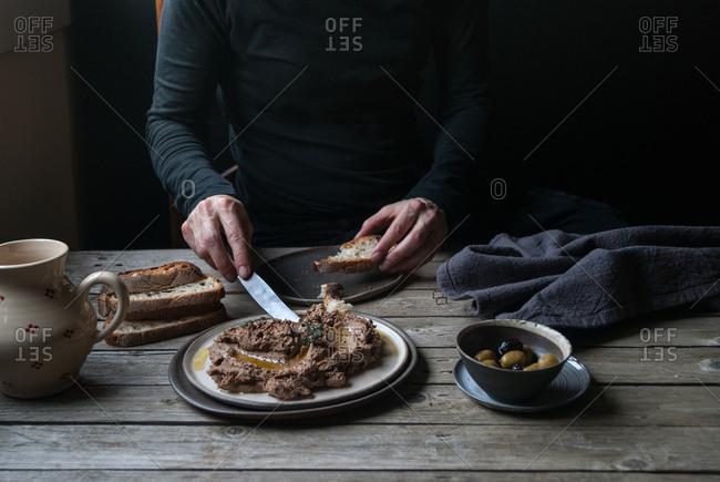 Man spreading lentil pate on bread