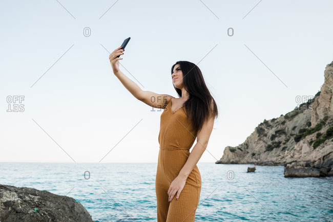 Trendy brunette in fashionable overall using phone camera and taking selfie on cliff of beautiful seascape