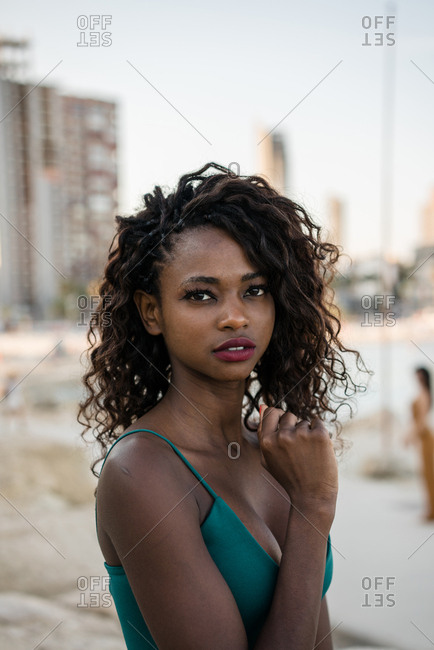 Young African-American woman with curls looking sensually at camera outside on coastline