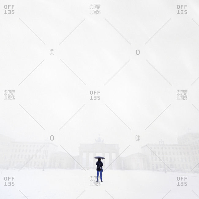 Rear view of a person standing on a snow covered landscape in Berlin during winter