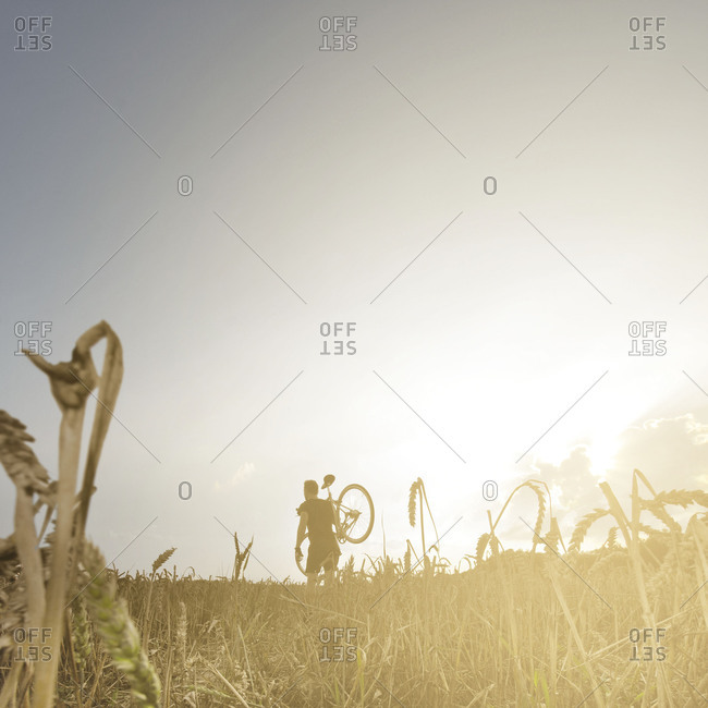 Male bicyclist walking in a field under clear skies out in nature