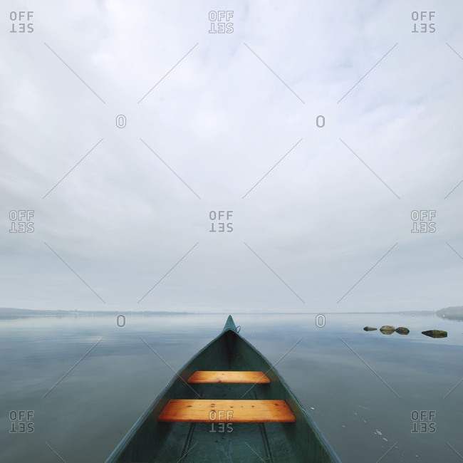 A canoe boat out at sea overlooking a grey horizon on a cloudy day