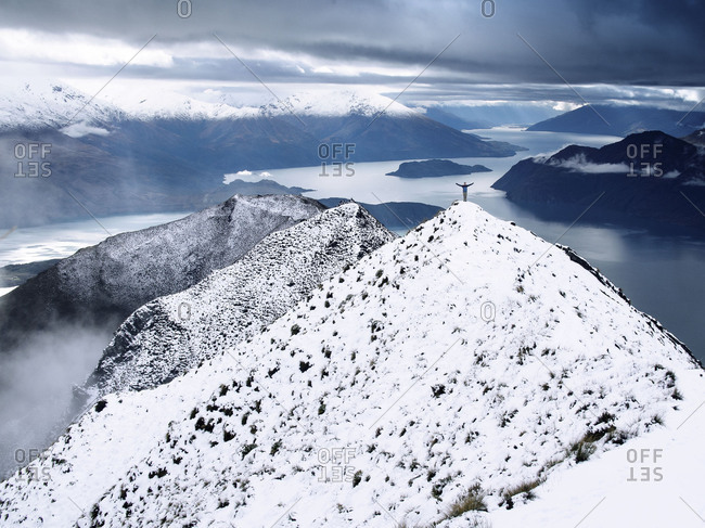 Scenic view of snowcapped landscape and person with arms wide open