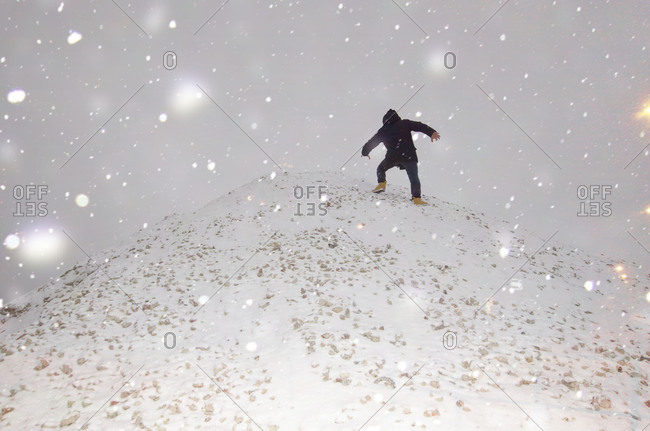 Low rear view of woman climbing mound in snow