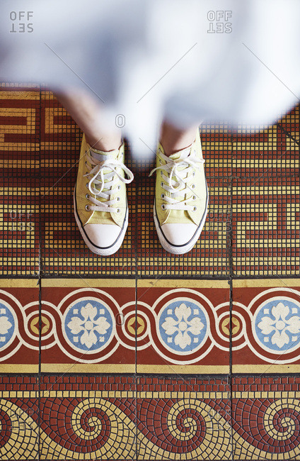 Woman wearing yellow sneakers standing on mosaic floor- partial view