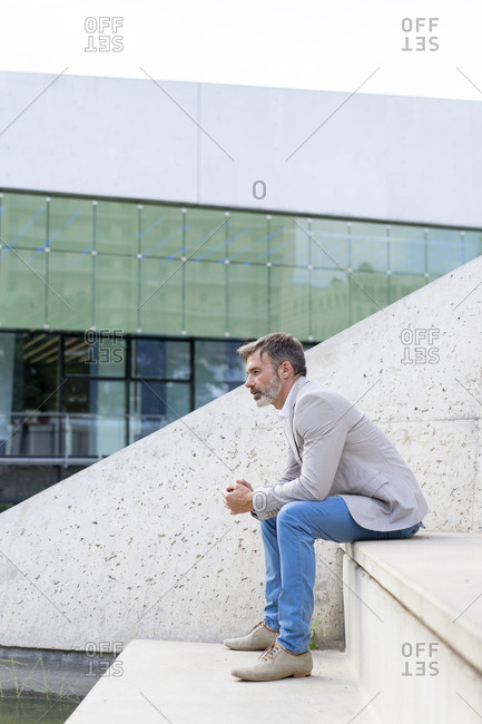 Pensive businessman sitting on steps outdoors