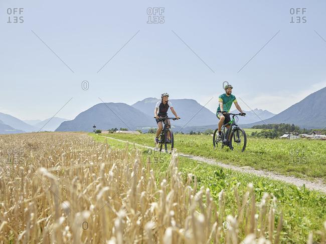 Austria- Tyrol- Mieming- couple riding bike in alpine scenery