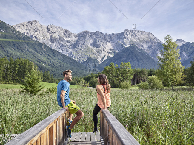 Austria- Tyrol- Mieming- couple resting on a boardwalk in the mountains