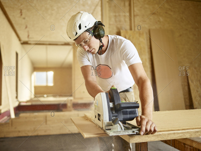 Worker with helmet sawing wood with circular saw
