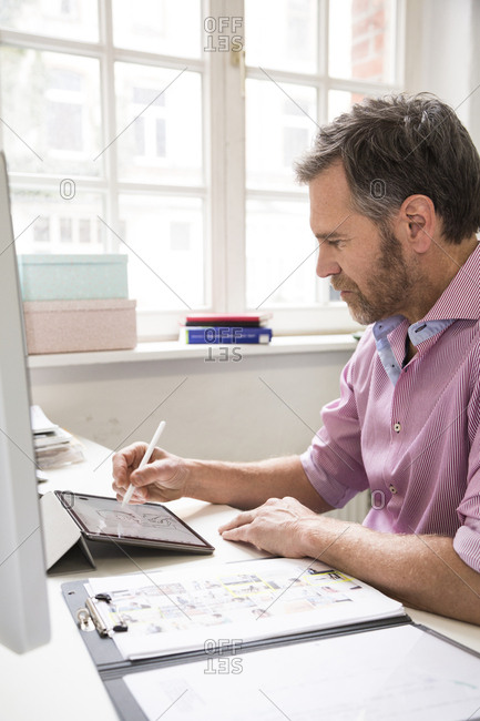 Man working at desk in office drawing on tablet