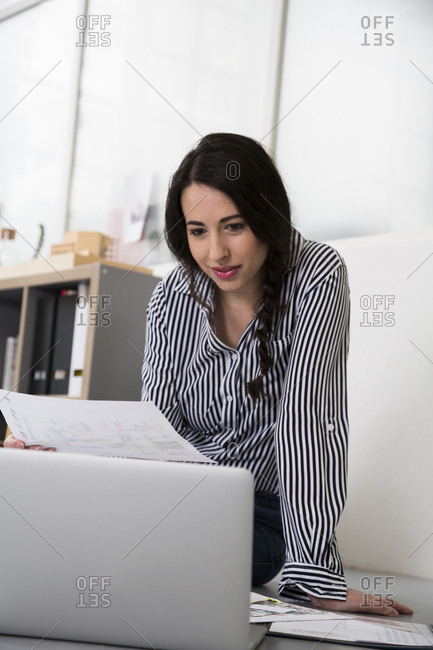 Casual woman with plans and laptop sitting on the floor in office