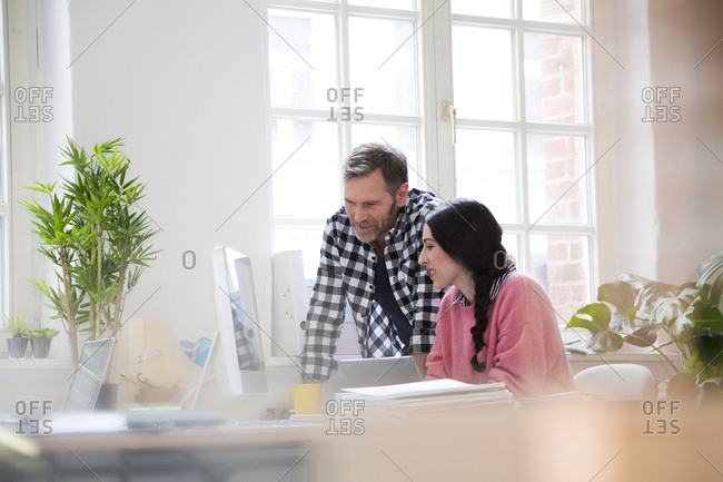 Colleagues discussing at desk in office