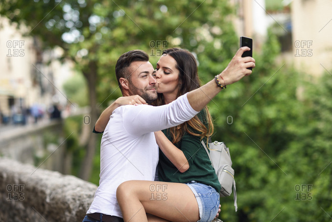 Couple in love in the city kissing and taking a selfie