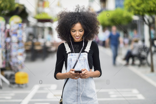 Smiling young woman with earphones looking at cell phone