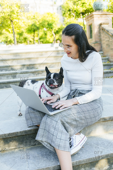 Woman using laptop next to her dog- sitting on stairs