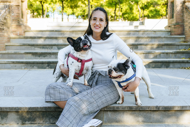 Portrait of woman sitting in the park with her two dogs