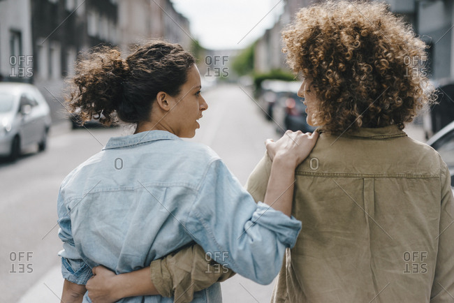 Best friends walking in the city- arm in arm- rear view