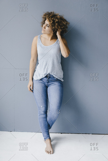 Woman leaning on wall with hand in hair