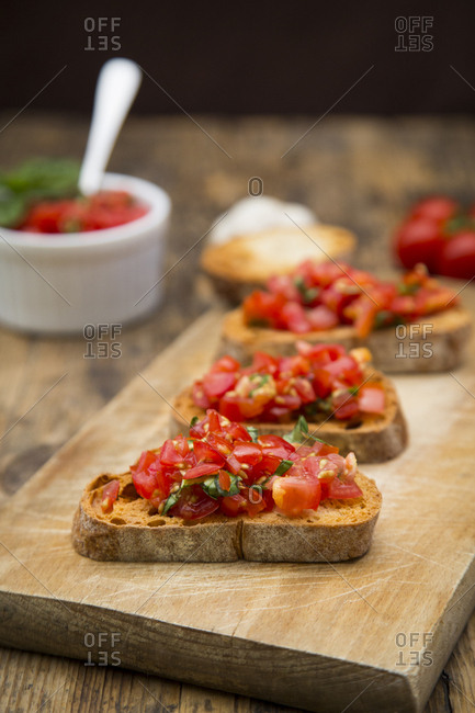 Bruschetta with tomato and basil on wooden board- close up
