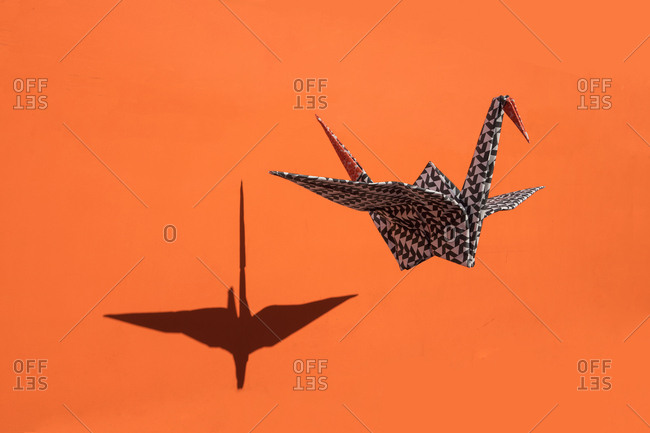 Origami crane- orange background- shadow- copy space