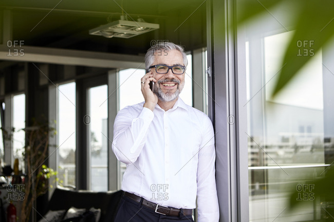 Smiling businessman standing at French door talking on cell phone