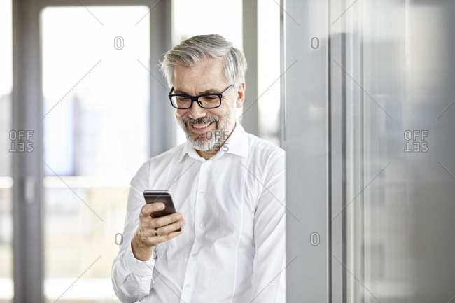 Smiling businessman at the window looking on cell phone