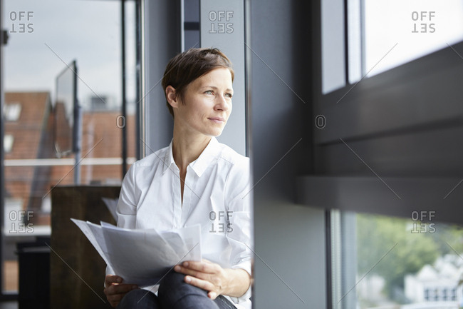 Businesswoman sitting in office with documents looking out of window