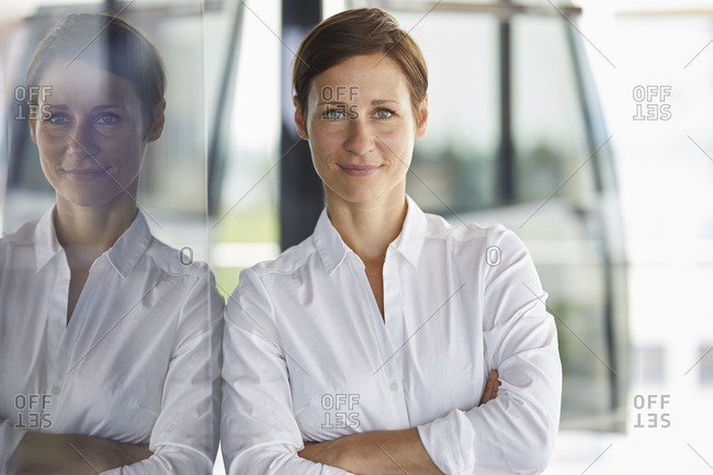 Portrait of smiling businesswoman leaning at glass pane in office