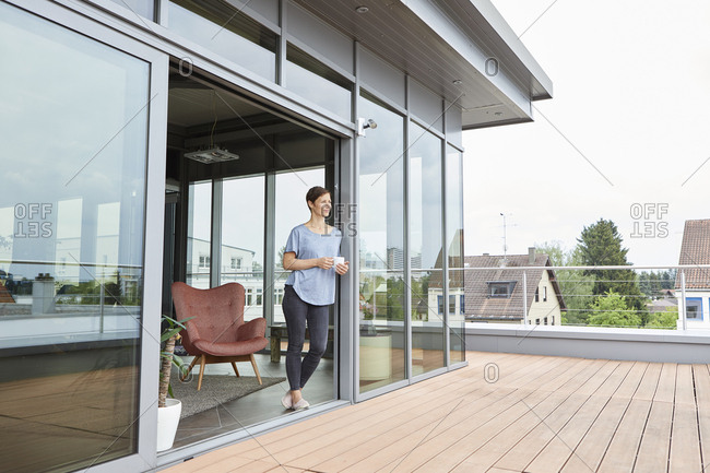 Woman at home with cup of coffee looking on roof terrace