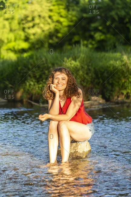 Young woman sitting on stone- river