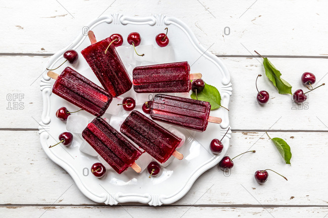 Homemade cherry ice lollies- ice cubes and cherries on plate