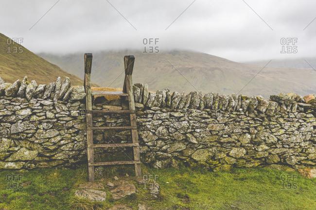 United Kingdom- England- Cumbria- Lake District- wood ladder- stone wall