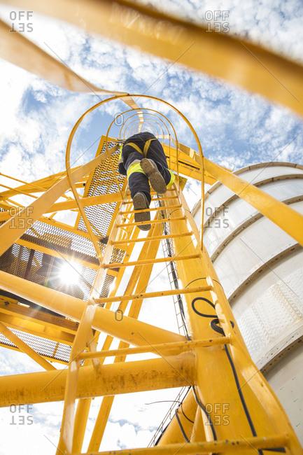 Worker climbing up ladder at tank