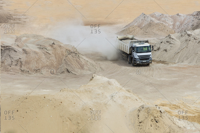 Truck driving through sand heaps