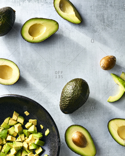Whole and sliced avocados with cut pieces in bowl