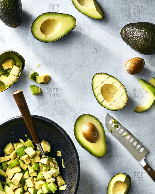 Sliced avocados in bowl with cut pieces in bowl