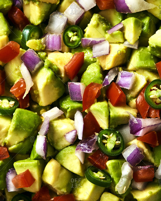 Close-up of freshly made guacamole with jalapenos, red onions, and tomatoes