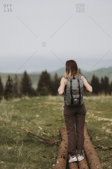 Back view of woman wearing backpack standing on fallen logs