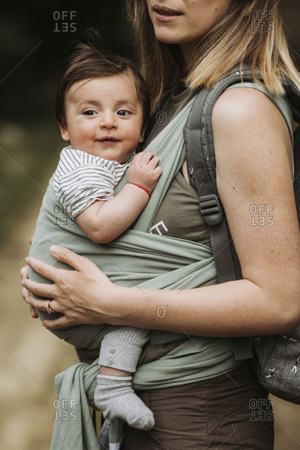 Mother carrying her baby in a wrap while hiking