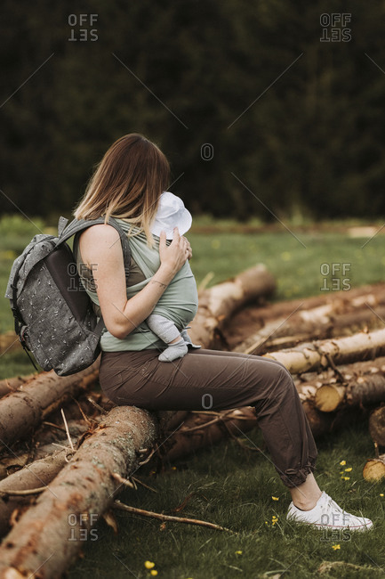 Woman sitting on a log holding her baby in a wrap while taking a break from hiking