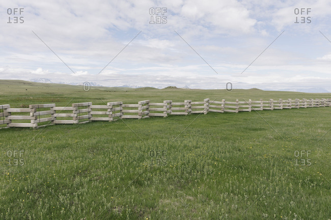 Concrete snow barrier, angled fencing across a verdant mountain meadow