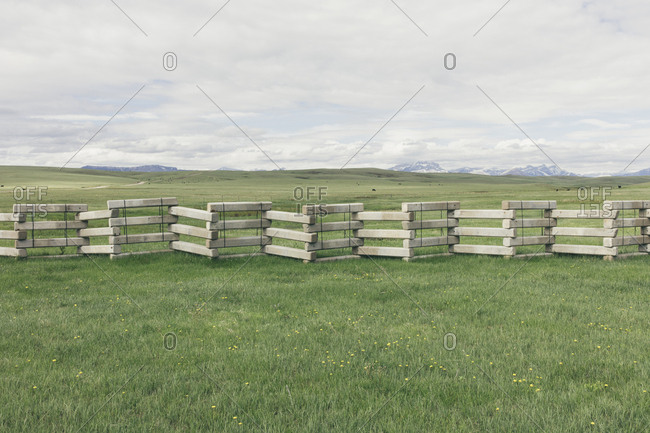 Concrete snow barrier and fencing across verdant mountain meadow