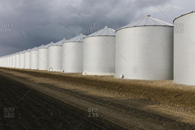 Rows of grain silos, stormy skies in distance, Saskatchewan, Canada