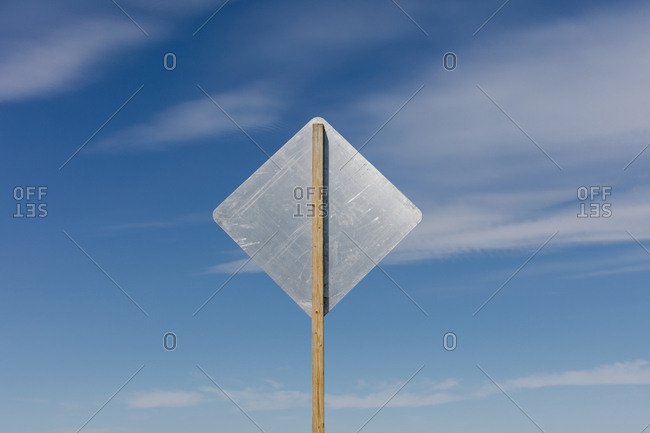 Blank side of a road sign, blue sky in background