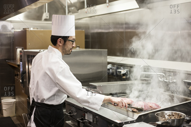 An asian chef working with fresh meat on the grill in a commercial kitchen,