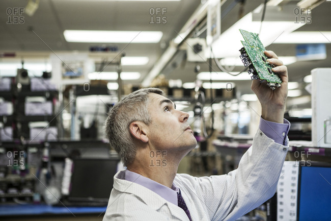 A caucasian male technician examining a circuit board in a technical research and development site